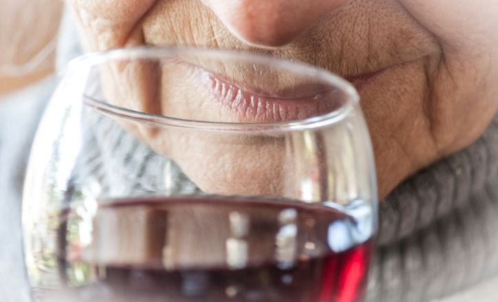 Woman smelling and drinking red wine